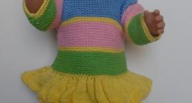 Dukketøj, børnevenligt, langærmet kjole med kort skørt strikket i lysegult, lysegrønt, lyserødt og lyseblåt garn
