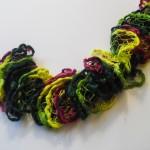 Tørklæder, dette tørklæde, der også kan anvendes som en boa, er strikket med effektgarn i gule, lilla og grønne nuancer