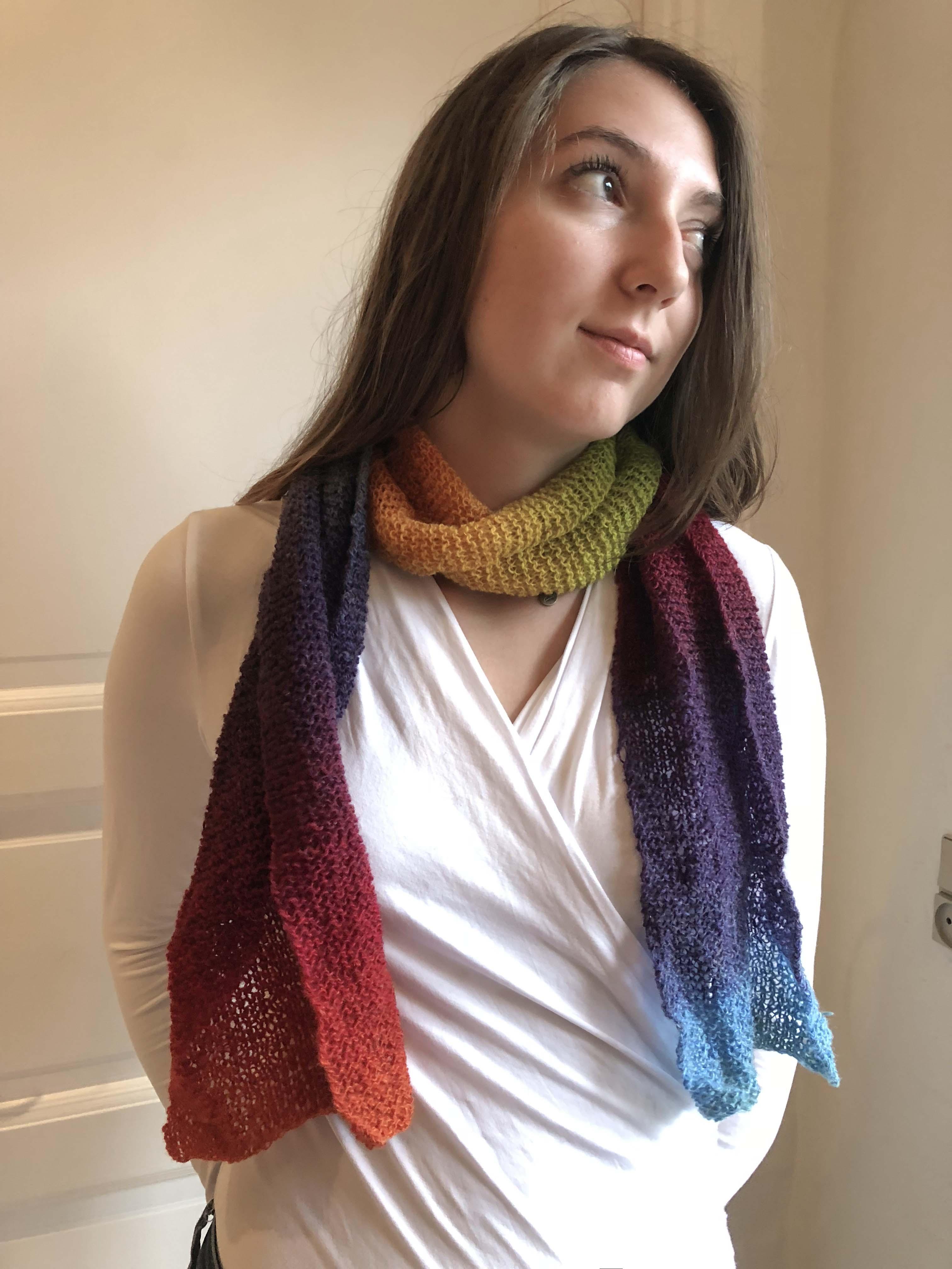 Smart tørklæde strikket i multifarvet tyndt uldgarn i nuancerne blå, lilla, rød, orange, gul og grøni nuancerne